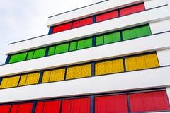 Elevación de un edificio de oficinas moderno con diversos colores de persianas en cada piso fotos de archivo