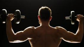 Elevación del culturista de la vista posterior pesas de gimnasia metrajes