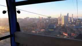 Elevación encima del teleférico en Batumi Visión desde la cabina en rascacielos, casas, y calles almacen de metraje de vídeo