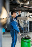 Elevación hidráulica sonriente de Repairing Car On del mecánico Fotos de archivo