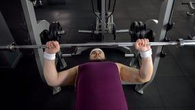 Elevación masculina regordeta encima de barbell, plan personal del entrenamiento del gimnasio, deseo de ser fuerte fotos de archivo libres de regalías