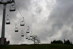 Elevación de silla del esquí que va para arriba una montaña en un día cubierto Imagen de archivo