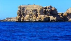 Elevado sobre nivel del mar, los arrecifes de coral hermosos las montañas de la forma y las rocas contra el cielo azul y la costa fotografía de archivo