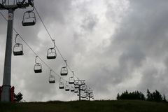 Elevador de cadeira do esqui que vai acima uma montanha em um dia nublado Imagem de Stock