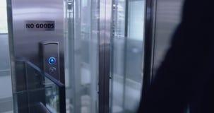 Elevador de espera do homem de negócios no corredor no escritório moderno 4k video estoque