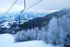 Elevador de esqui à parte superior das montanhas Carpathian neve-tampadas no inverno Imagens de Stock