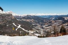 Elevador de esqui amarelo do teleférico que vai acima na parte superior da montanha Fotos de Stock Royalty Free