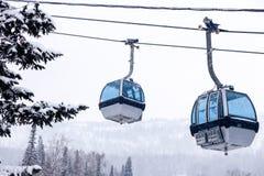 Elevador de esqui no teleférico com uma cabine fechado com o azul espelhado fotografia de stock
