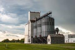 Elevador de grão de madeira velho contra o céu dramático Fotografia de Stock Royalty Free