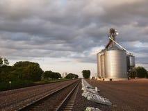 Elevador de grano por las vías del tren foto de archivo