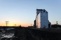 Elevador e trilha de grão no nascer do sol Imagem de Stock