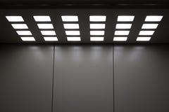 Elevador gris del metal con las lámparas cuadradas en el techo imagen de archivo libre de regalías