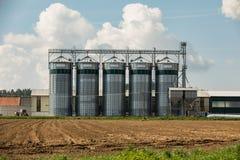 Elevador para armazenar a grão em um campo na terra Imagens de Stock