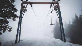 Elevador vazio da t-barra na névoa nas montanhas fotografia de stock
