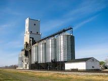 Elevador y compartimientos de grano con el cielo azul foto de archivo