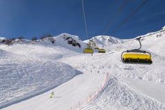 Elevadores de cadeira do liftYellow do esqui contra as montanhas bonitas imagens de stock royalty free