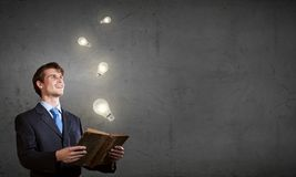 Elevate your mind. Young handsome man in suit reading old book stock photography