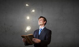 Elevate your mind. Young handsome man in suit reading old book royalty free stock image
