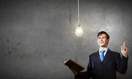 Elevate your mind. Young handsome man in suit reading old book stock images