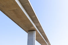 Elevated concrete road bridge from below with plain blue sky. An elevated concrete road bridge seen from below. Supported by a single visible pillar. Blue sky Royalty Free Stock Photography