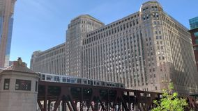 Elevated `el` train, Chicago`s transit system, stopped on the Wells Street bridge over the Chicago River. During colorful summer evening in Chicago stock video footage