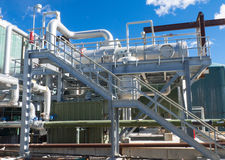 Elevated heat exchanger. Insulated heat exchanger on a hot dipped galvanized skid with stairs inside an industrial facility Stock Photos