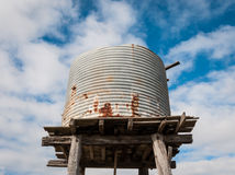 Elevated old water tank. Rusty disused water tank elevated on a weathered timber platform Royalty Free Stock Photo