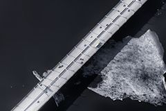 Elevated road over sea aerial view. Elevated road over cold sea with ice aerial view. Dark toned image royalty free stock photo