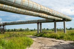 Elevated section of the pipelines above the dirt road Stock Images