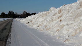 Elevated soil all covered in snow. A large snowy hill on the roadside of the street. Elevated soil all covered in snow. An elevated ground at the side of the stock video footage