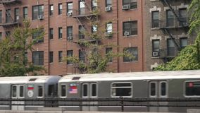 Elevated Subway Trains Pass Harlem Apartment Buildings. 9410 Two New York City subway trains pass by Harlem apartment buildings on an elevated track stock video footage