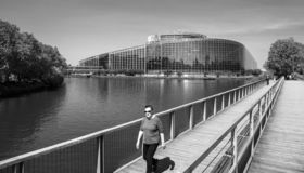 Elevated view of adult woman walking European Parliament background royalty free stock image
