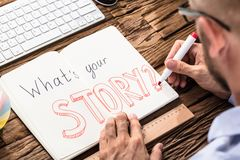 Businessman Asking What`s Your Story On Notebook. Elevated View Of Businessman Asking What`s Your Story On Notebook Over The Office Desk stock photo