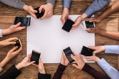 Elevated View Of Businesspeople Hand Using Mobile Phone stock photo
