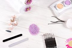 Elevated view of colorful sea salt, towels, flowers, nail polishes, cream container, nail clippers, cuticle pusher, nail files. And samples of nail varnishes stock image