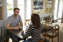 Elevated view of couple talking at a table in a coffee shop Royalty Free Stock Photo