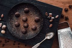 elevated view of cutting board with truffles on plate covering by grated chocolate, spoon, cocoa beans, nutmegs, anise and grater stock images