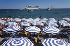 Elevated view of famous beach umbrellas of Amalfi with cruise ship in background in the province of Salerno, Amalfi, Italy, Europe Stock Photography