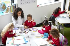 Elevated view of female kindergarten teacher sitting at a table helping four children during a lesson royalty free stock photo
