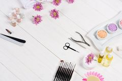 Elevated view of flowers, nail polishes, nail files, scissors, cuticle pusher, nail clippers, aroma oil bottles, sea salt, cream,. Tools for manicure and stock photo