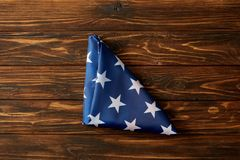 Elevated view of folded united states flag on wooden surface stock photos