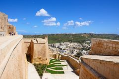 Citadel buildings and town rooftops, Victoria, Gozo. Elevated view of fortified buildings and the landscaped old moat within the citadel with views towards the Stock Image