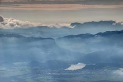 Sunny autumn panorama of hazy Lake Bled in Slovenia. Elevated view through glowing autumn mist and sunbeams to Lake Bled, Bohinj mountain range and Pokljuka Royalty Free Stock Image