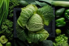 Elevated view of green savoy cabbage in wooden box between vegetables, healthy. Eating concept royalty free stock images