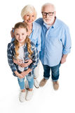 Elevated view of happy grandfather, grandmother and grandchild hugging and looking at camera. Isolated on white Stock Photography