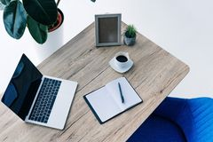 Elevated view of laptop with blank screen, empty textbook, photo frame, potted plant and coffee cup. On table royalty free stock photos