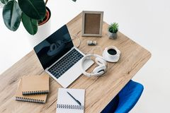 Elevated view of laptop with blank screen, headphones, textbooks, photo frame, roll of money, potted plant, coffee cup. On table stock images