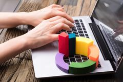 Elevated View Of Multi Colored 3d Pie Chart. Businesswoman Using Laptop With Multi Colored 3d Pie Chart stock photos