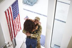 Elevated view of returning African American  male soldier embracing his wife in the doorway of their home. Elevated view of returning black male soldier royalty free stock image