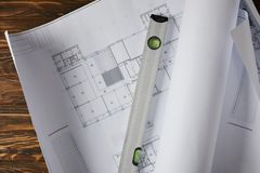 Elevated view of spirit level on blueprint at wooden table royalty free stock images